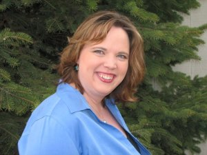 Profile photo of Michelle McMullin. Wearing Blue Button down, standing in front of large pine tree.